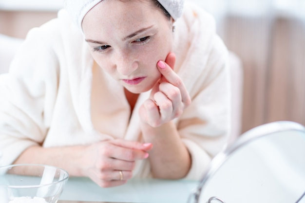 Beautiful happy young woman with a towel on head looking at her skin in a mirror. timely hygiene and care for the skin Premium Photo