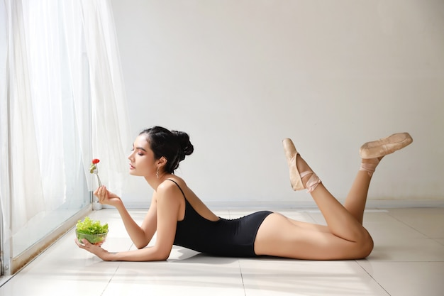 Beautiful healthy asian young woman eating salad after training ballet while lying down Premium Photo