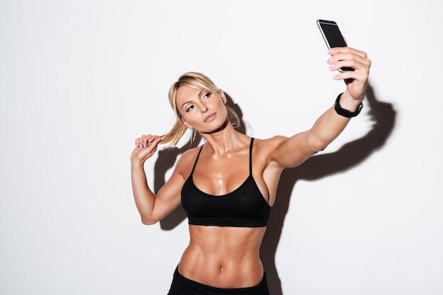 Bella sportiva in buona salute che prende un selfie mentre stando Foto Gratuite