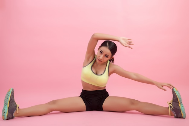 Beautiful healthy young asian woman doing a stretching exercise before playing a sport. Free Photo
