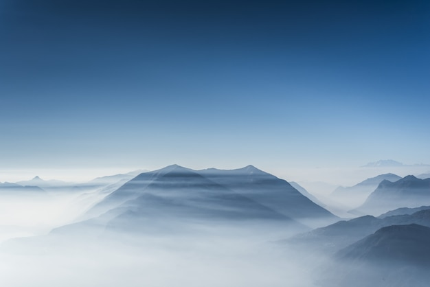 Beautiful hilltops covered in fog and clouds with clear blue sky Free Photo