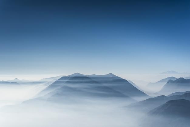 맑고 푸른 하늘과 안개와 구름으로 덮여 아름다운 언덕 무료 사진
