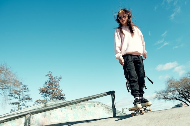 Beautiful hipster girl with casual clothes and long straight hair is skating on a ramp with her skateboard in the skate park Premium Photo