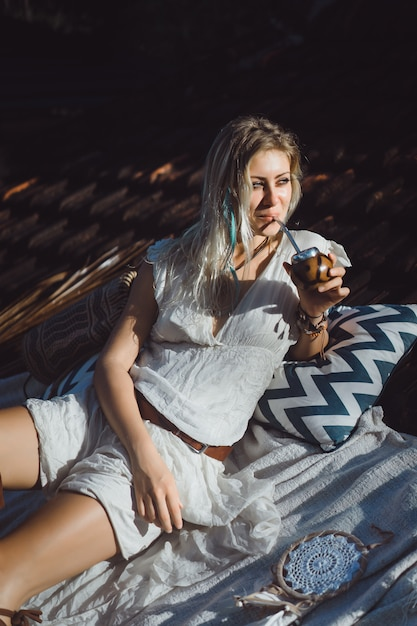 Beautiful indian hippie girl with long blond hair on the roof drinking mate tea. Free Photo