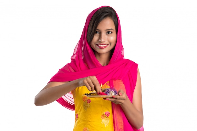 Beautiful indian young girl holding pooja thali or performing worship on a white space Premium Photo