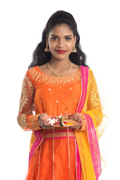Beautiful indian young girl holding pooja thali or performing worship on a white wall Premium Photo