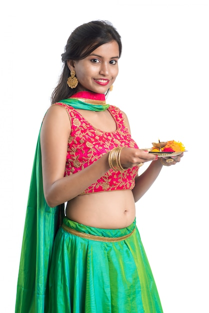 Beautiful indian young girl holding pooja thali or performing worship on a white Premium Photo
