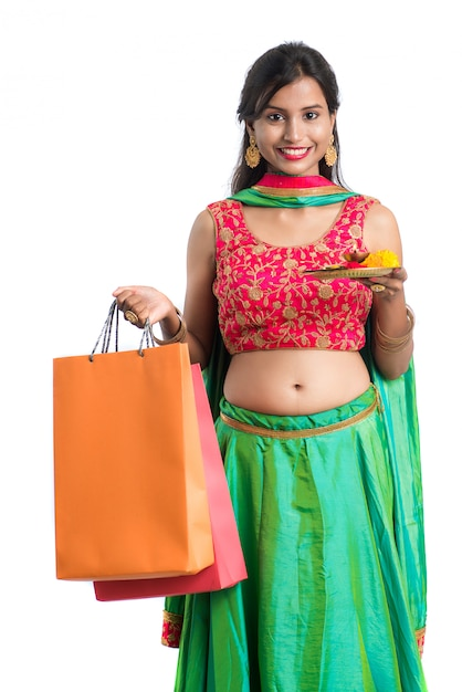 Beautiful indian young girl holding and posing with shopping bags and pooja thali on a white space Premium Photo