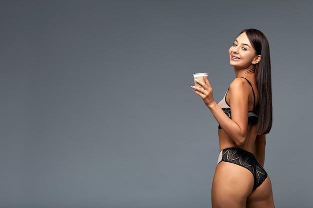 Красивая итальянская женщина с кофе в нижнем белье, на сером фоне с копией пространства. Premium Фотографии