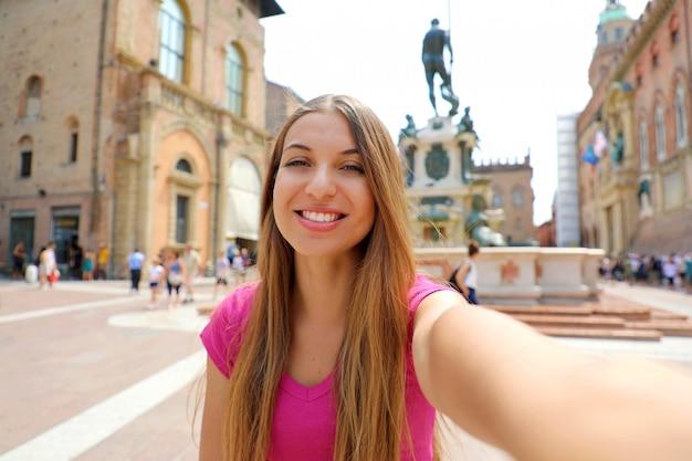 美しいイタリア。魅力的な笑顔の若い女性は、イタリアのボローニャ市ネッツォ広場広場でセルフポートレートを取る。 Premium写真
