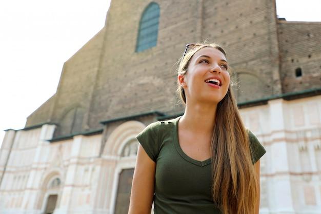 美しいイタリア。背景にサンペトロニオ教会とボローニャの中世都市でかなり若い観光客の女性。イタリアの観光コンセプト。 Premium写真