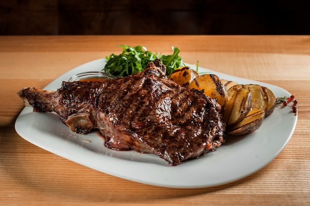 A beautiful juicy steak with salad on  plate is on the wooden table. Premium Photo