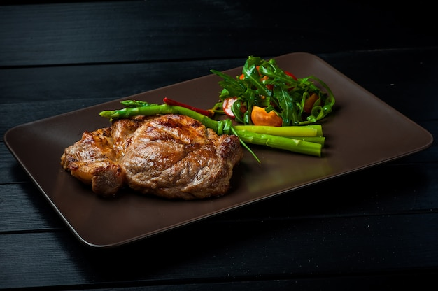 A beautiful juicy steak with salad on a straight brown plate is on the table. Premium Photo