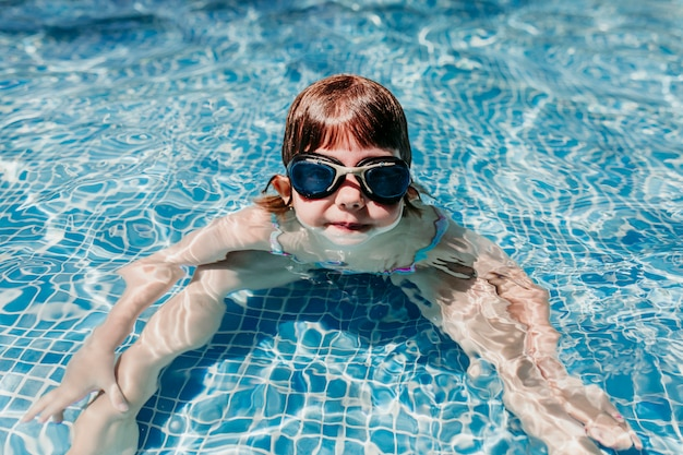 Beautiful kid girl at the pool diving with water goggles. fun outdoors. summertime and lifestyle concept Premium Photo