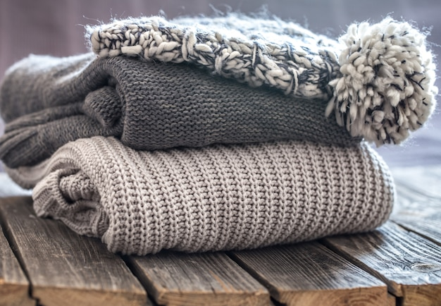 Beautiful knitted clothes, neatly folded, close-up, handmade sweaters. Free Photo