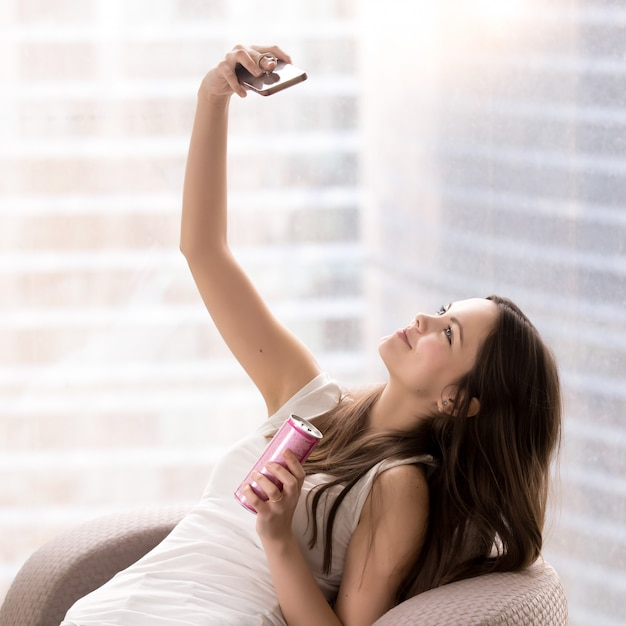 Beautiful lade in armchair making selfie Free Photo