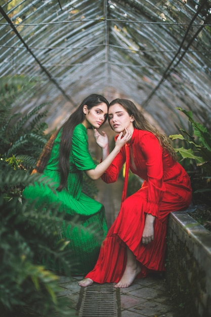 Beautiful ladies in dresses posing in a green house Free Photo