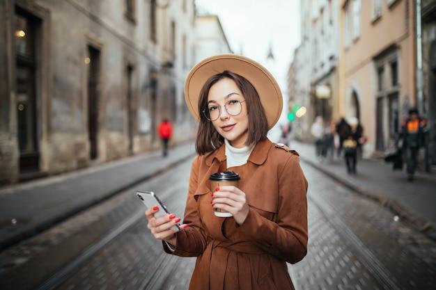 美しい女性がビデオ通話をしていて、街の屋外を歩きながらコーヒーを飲む 無料写真