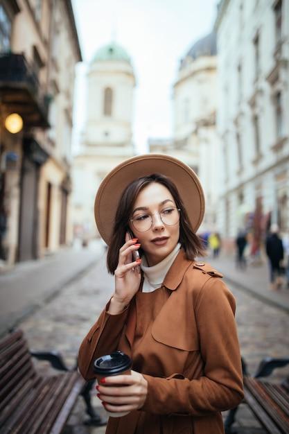 Красивая дама в коричневом пальто разговаривает по мобильному телефону гуляя на улице в холодный осенний день Бесплатные Фотографии
