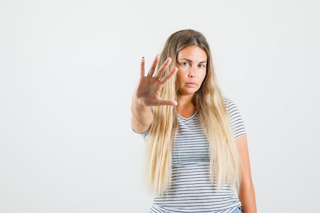 Красивая дама показывает жест остановки в футболке и выглядит серьезно. передний план. Бесплатные Фотографии