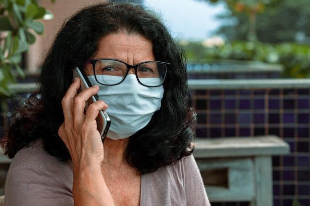 パンデミックから保護されたサージカルマスク付きの携帯電話で話している美しい女性 Premium写真