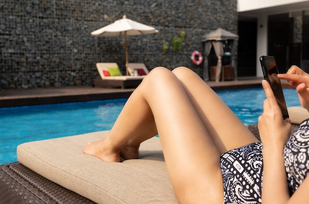 Beautiful lady using cell phone lying on chair by swimming pool on vacation. Premium Photo