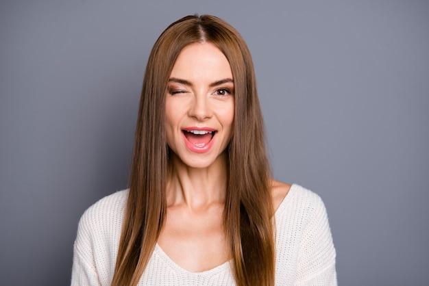 灰色の壁にポーズをとって長い髪の美しい女性 Premium写真