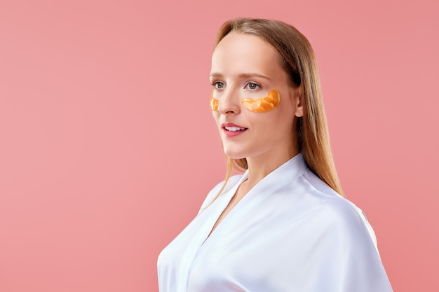 Beautiful lady with mask for the skin around the eyes in profile Premium Photo