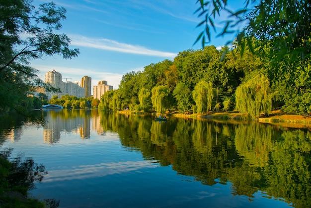 水面に木々が映る夏の美しい湖。キエフの美しい都市公園 無料写真