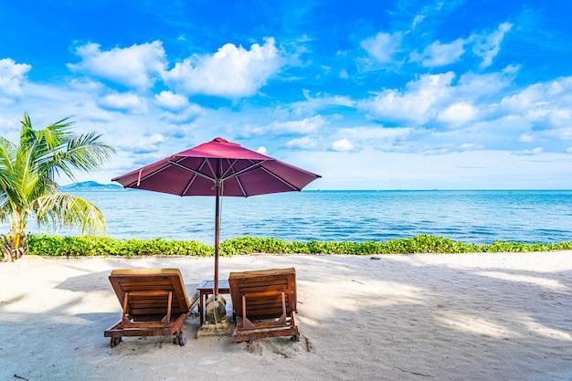 Bello paesaggio dell'oceano del mare della spiaggia con la piattaforma e l'ombrello vuoti della palma quasi del cocco con la nuvola e il cielo blu bianchi Foto Gratuite