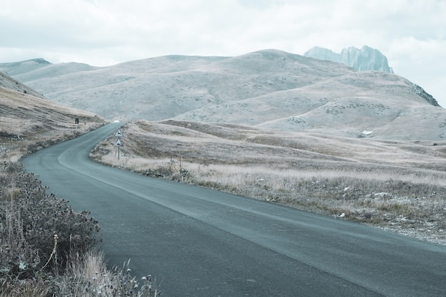 曇りの日に丘を転がる道の美しい風景 無料写真