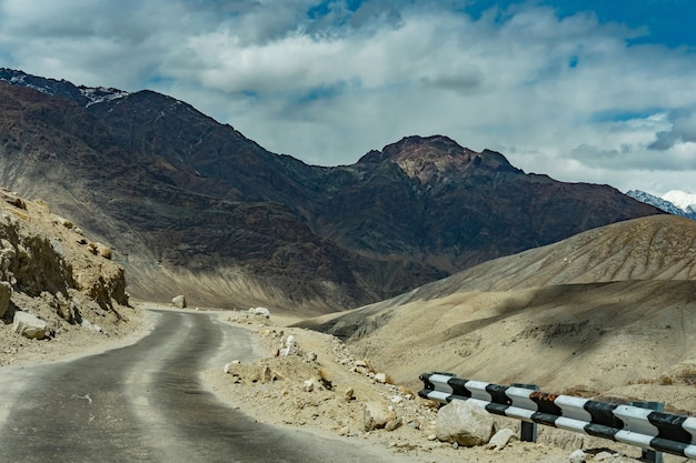 Beautiful landscape of road on the way in the hill with snow mountain background, ladakh Premium Photo
