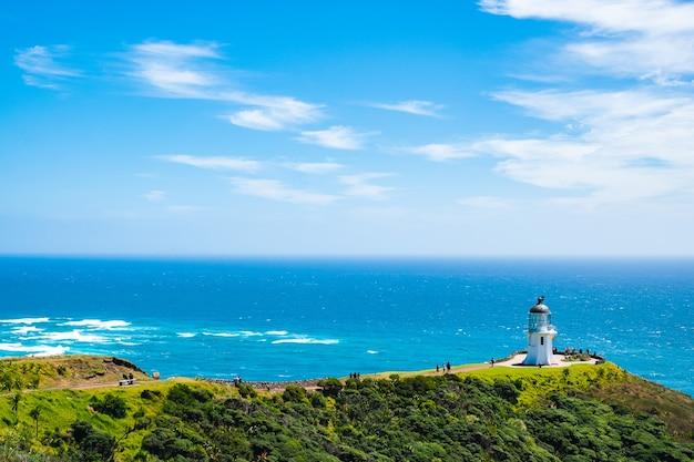 緑の山の青い空と灯台、歴史的建造物の美しい風景。ニュージーランド、北島、レインガ岬。 Premium写真