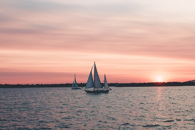 Beautiful landscape shot of sailboats in the sea under pink sky Free Photo