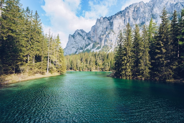 Beautiful landscape with a lake in a forest and amazing high rocky mountain Free Photo