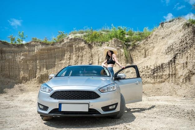 夏休みの砂浜でポーズをとる車の近くの美しい脚 Premium写真