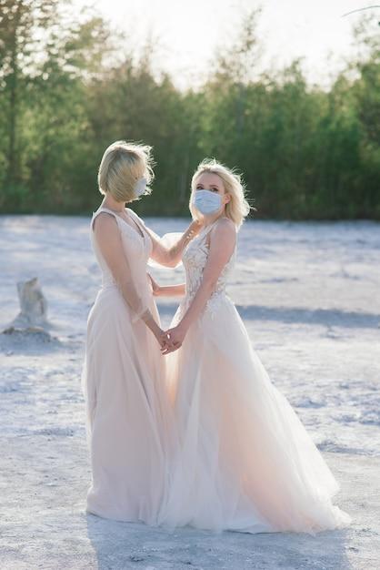 彼らの結婚式の日に川岸に沿って砂の上を歩く美しいレズビアンのカップル Premium写真