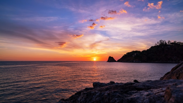 自然の美しい光夕日の風景の背景の手前の岩と劇的な空の海。 Premium写真