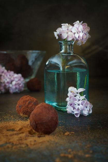 Bellissimo bouquet lilla in una bottiglia di vetro blu e deliziosi cioccolatini Foto Gratuite