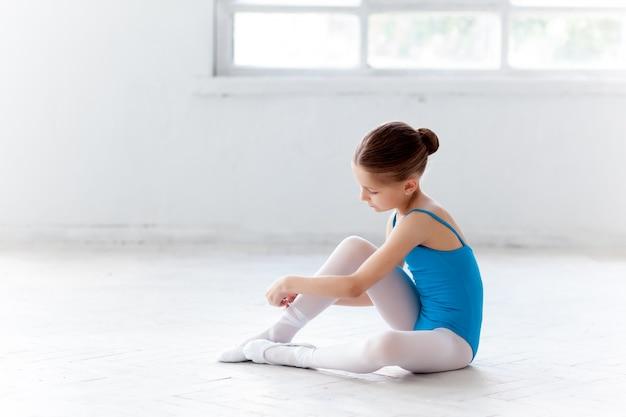 ポアントシューズを履いて踊るための青いドレスの美しい小さなバレリーナ 無料写真