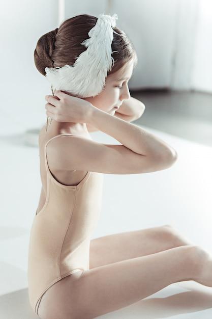 彼女の頭に白い白鳥の包帯を着て美しい小さなバレリーナ 無料写真