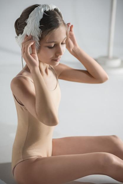 彼女の頭に白い白鳥包帯を身に着けている美しい小さなバレリーナ 無料写真