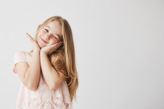 아름 다운 작은 금발 소녀 윙크, 포즈, 분홍색 귀여운 드레스에 그녀의 손으로 얼굴을 만지고 미소. 행복하고 기쁘게 보는 아이. 공간을 복사하십시오. 무료 사진