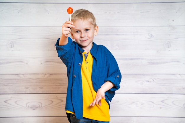 Beautiful little boy with a lollipop in hands Premium Photo