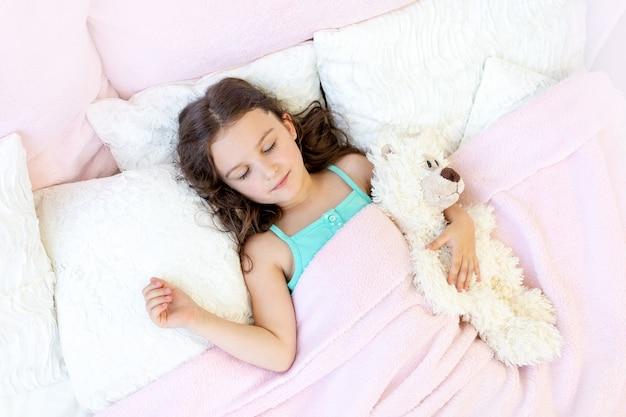 テディベアとベッドで寝ている5-6歳の美しい少女 Premium写真