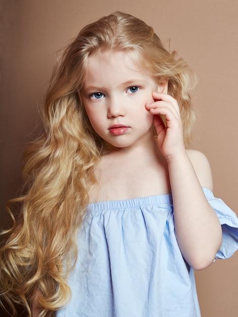 Beautiful little girl blonde curly hair, bright | Premium ...