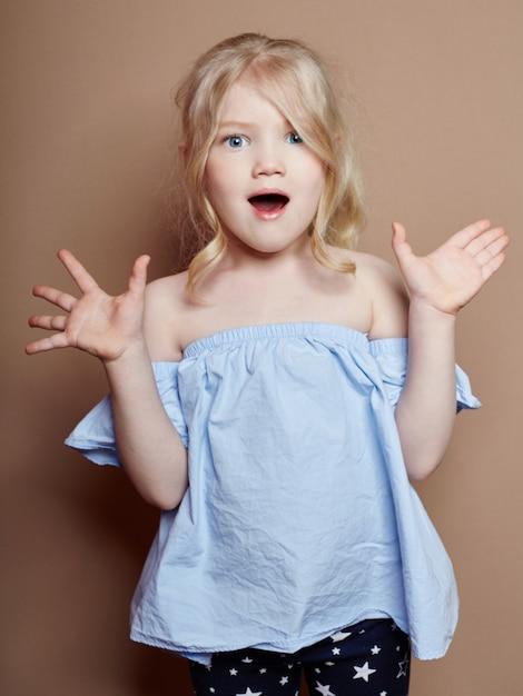 Beautiful little girl blonde curly hair, emotions Premium Photo