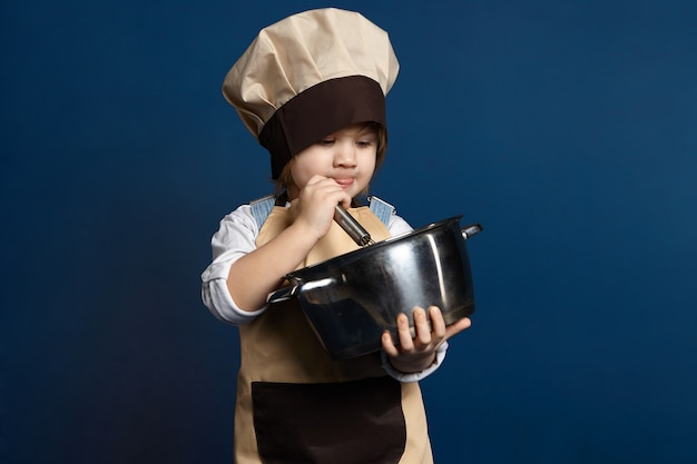 Cuoco unico bello della bambina che cucina qualcosa in casseruola. concentrato di bambina di 5 anni in grembiule e cappello che monta diligentemente gli albumi mentre prepara l'impasto dei biscotti per la pasticceria. concetto di cottura Foto Gratuite