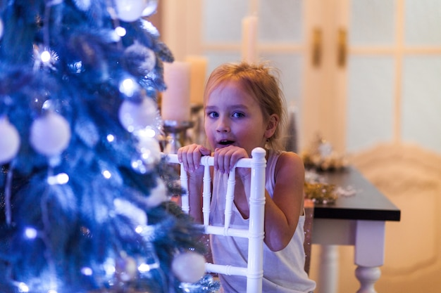 Beautiful little girl in christmas decorations and waiting for santa Premium Photo