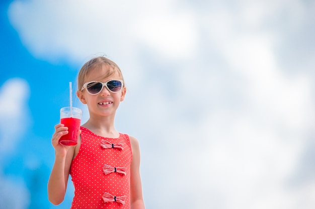 Beautiful little girl drinking cocktail on tropical beach Premium Photo